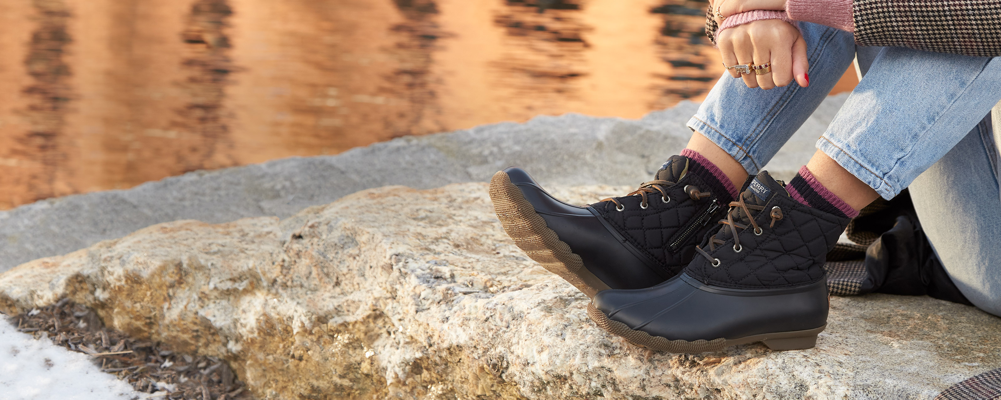 A woman's legs crossed sitting on a stone wall overlooking a river; rubber and leather duck boots on her feet