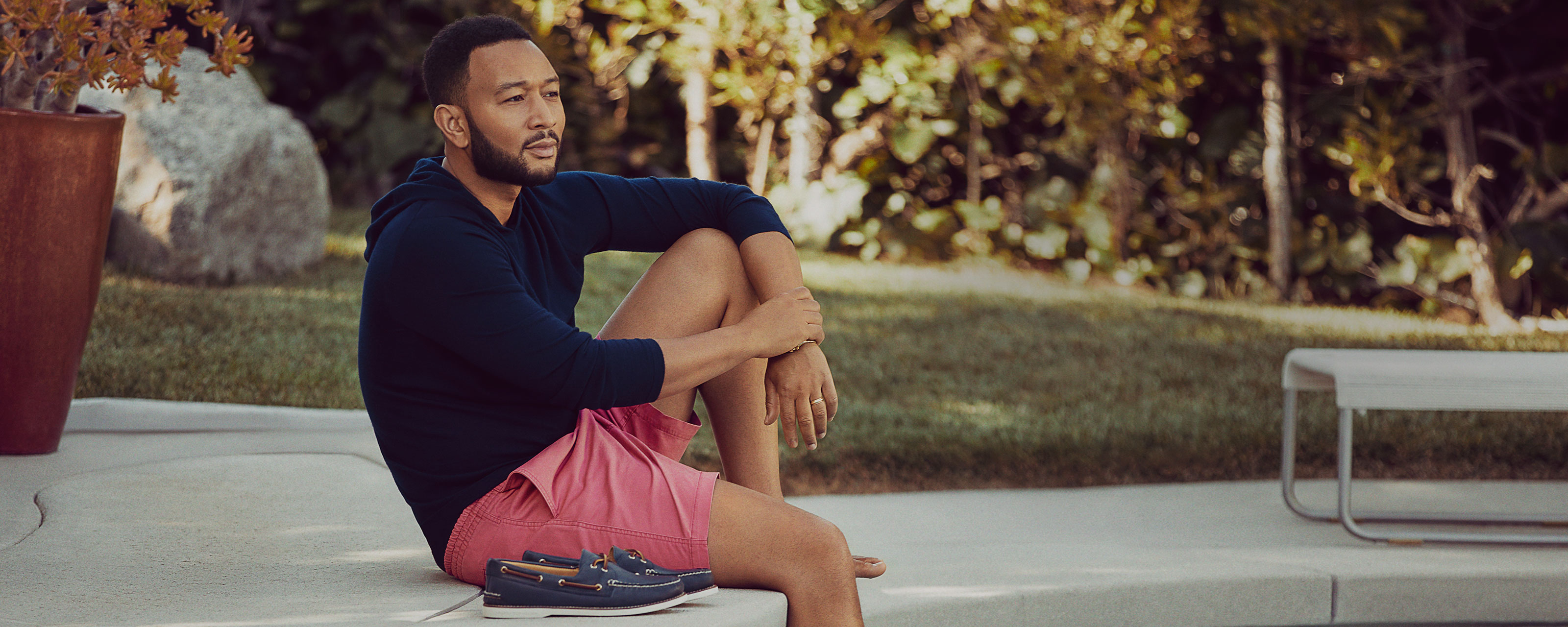 John Legend sitting at a pool, wearing Sperry Boat Shoes.