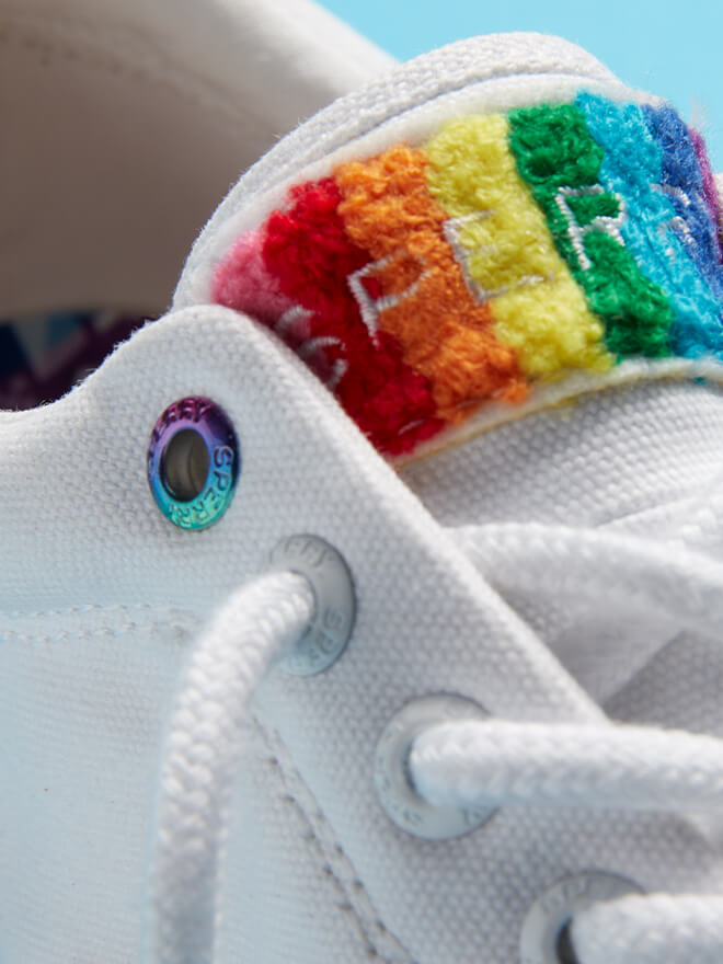 White canvas shoe with rainbow Sperry logo on tongue.