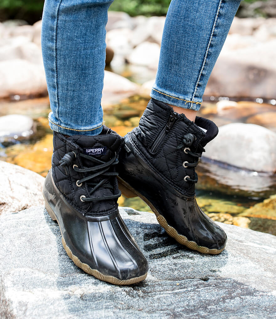 Fleece-lined boots worn along a rocky riverbed.