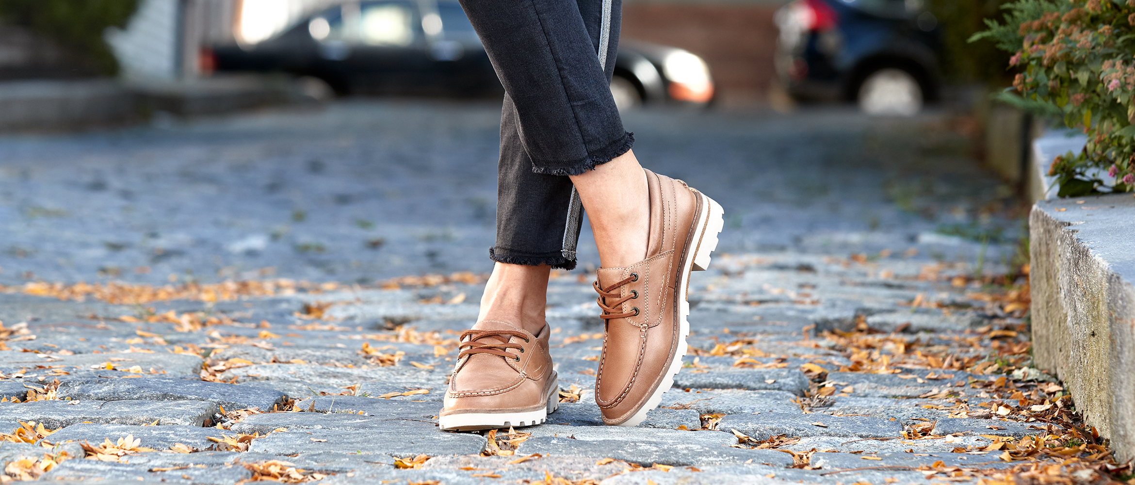 A pair of crossed women's lug shoes on a cobble stone street with leaves strewn about.