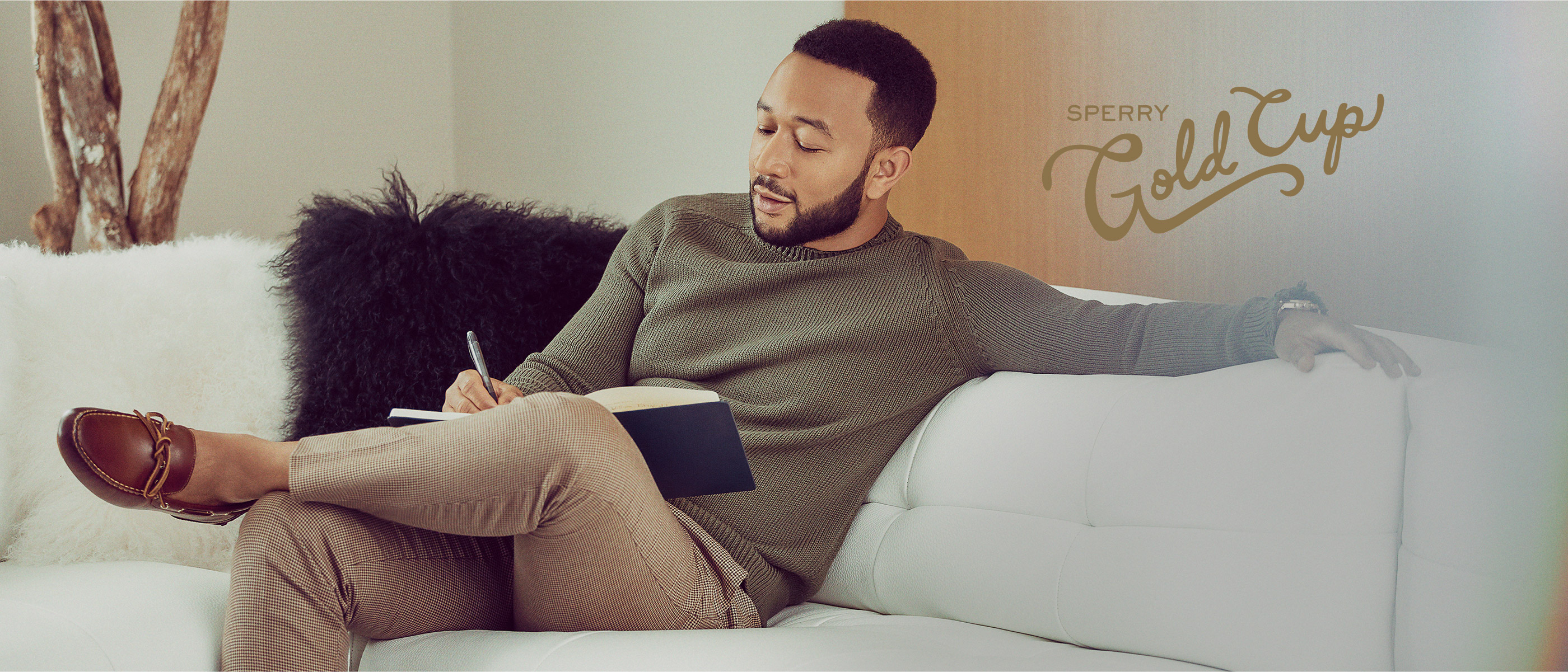 John Legend sitting on a white couch with his legs crossed writing in a book on his lap.