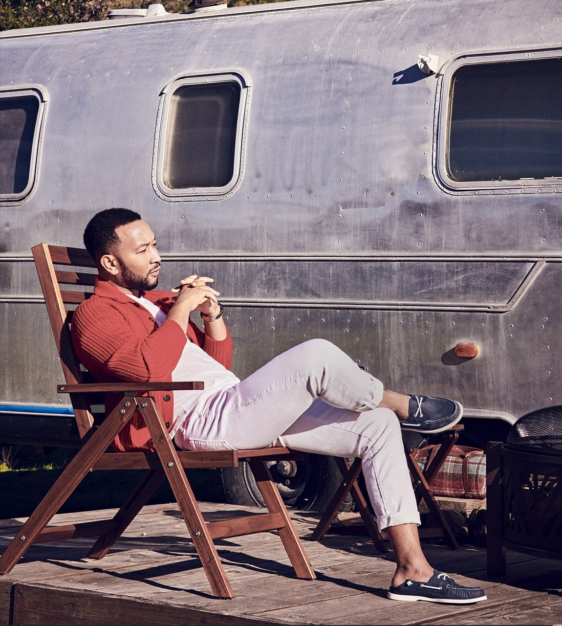 John Legend sitting on in a chair next to a trailer, wearing Sperry Boat Shoes.