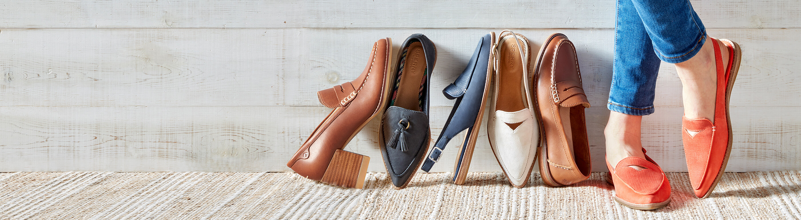Casual feet stand beside loafers in a variety of styles and colors leaning against a wall.