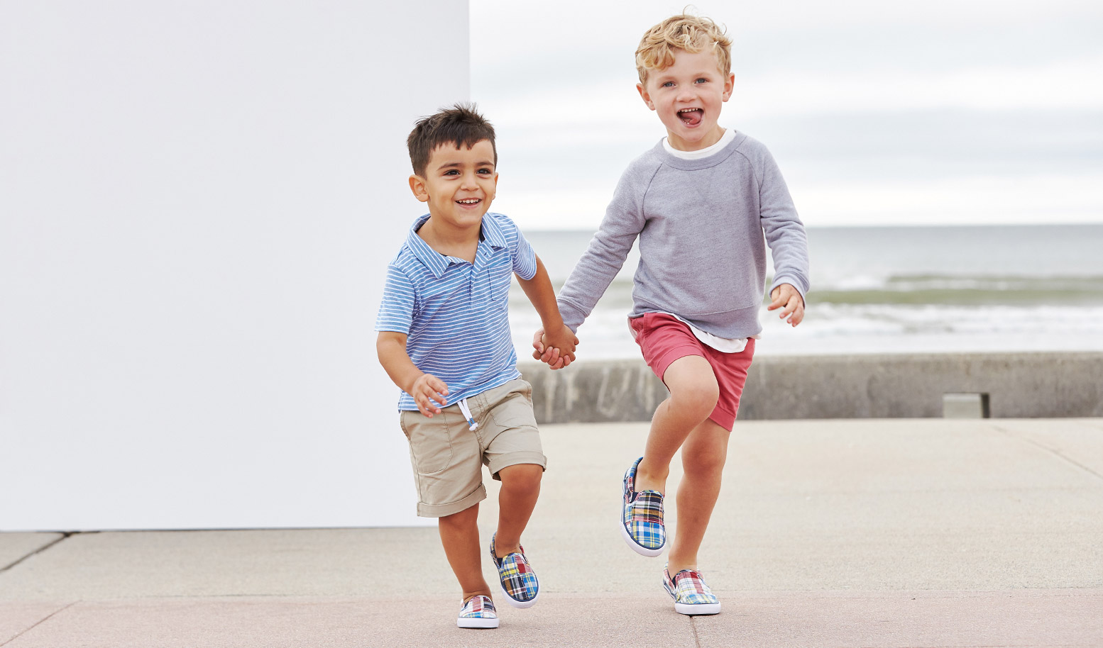 Two kids holding hands and running on a boardwalk in their Sperry loafers.