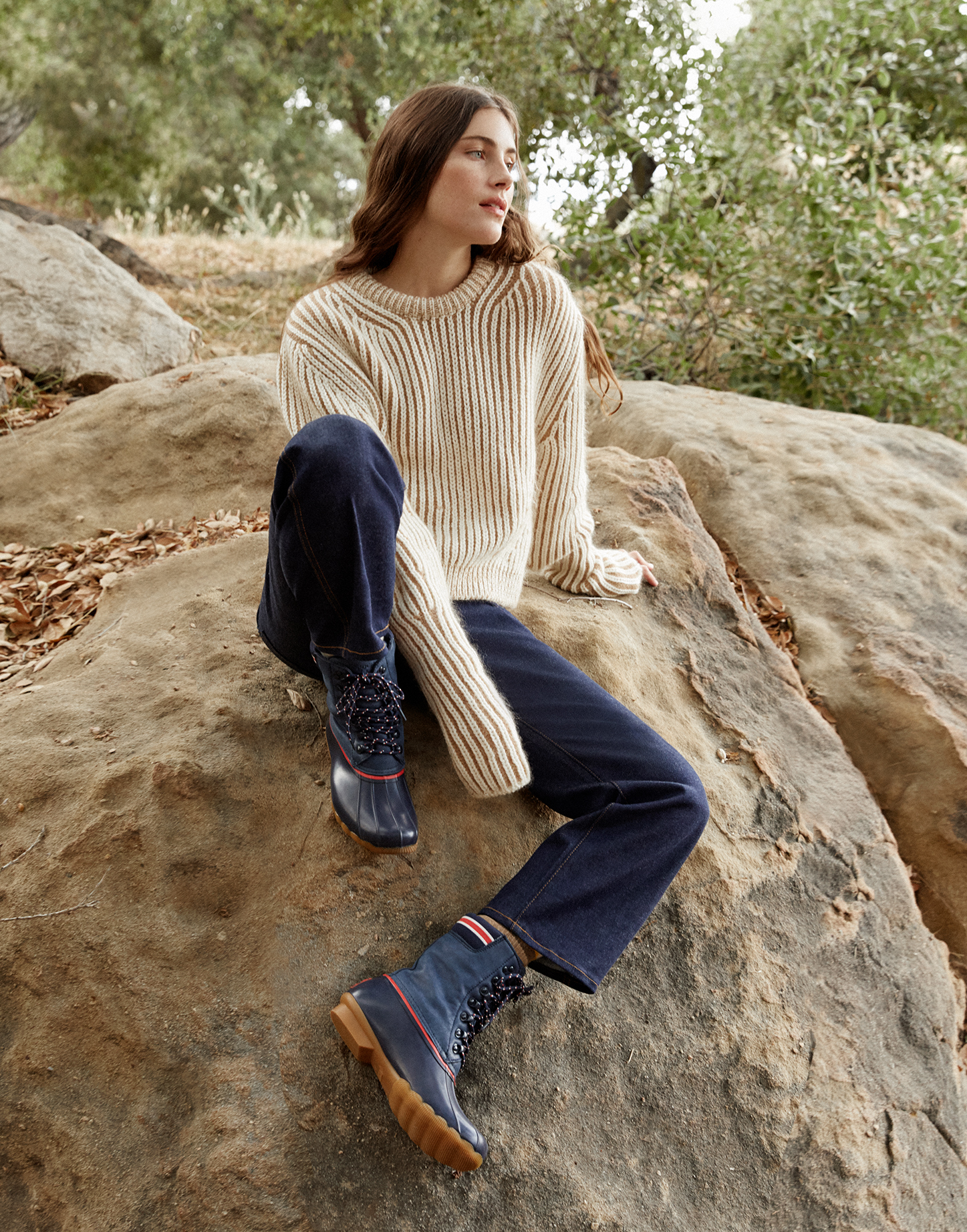Woman wearing Goop & Sperry boots while sitting on a rock.