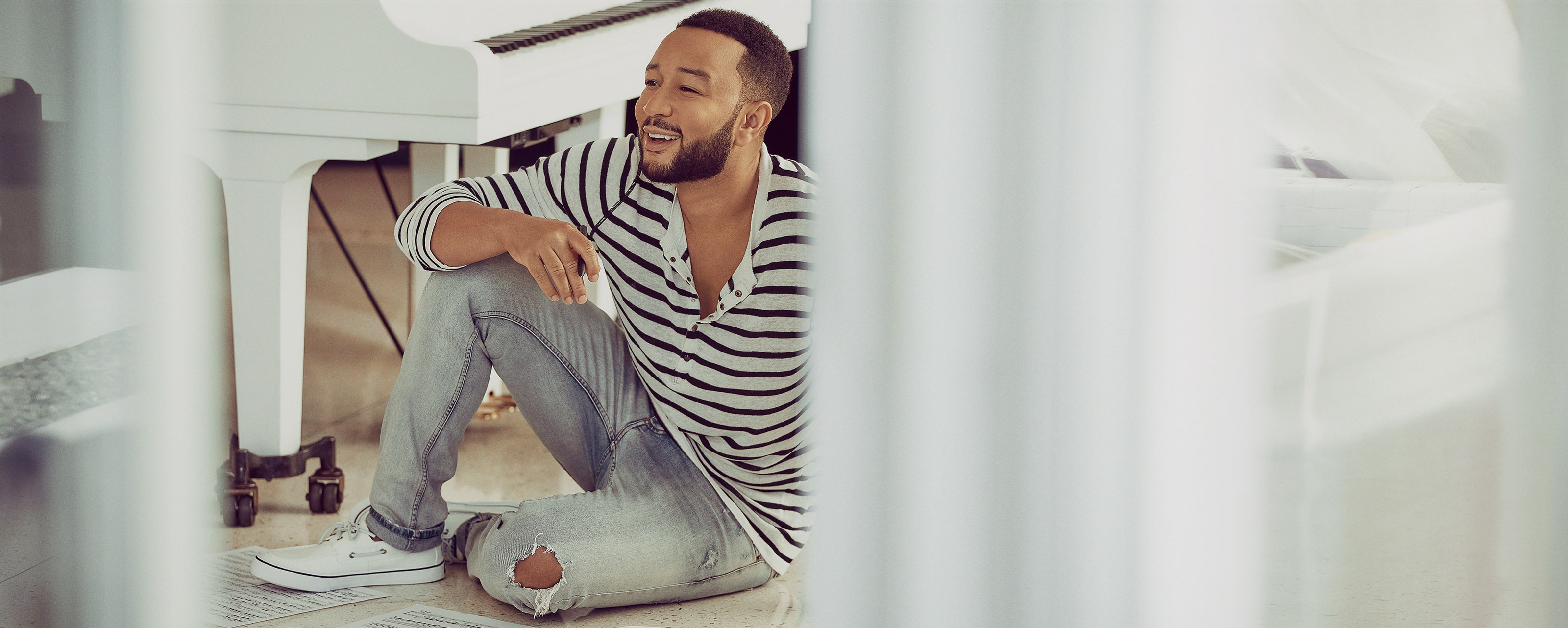 John Legend sitting by a piano, wearing Sperry Boat sneakers.