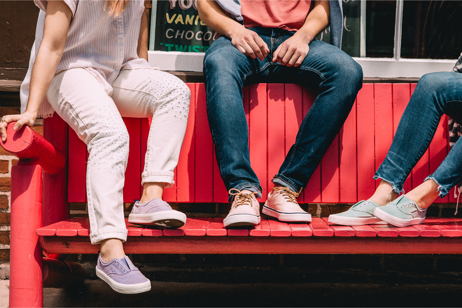 People sitting on the back of a bench with their feet on the seat, wearing Sperry casual sneakers.