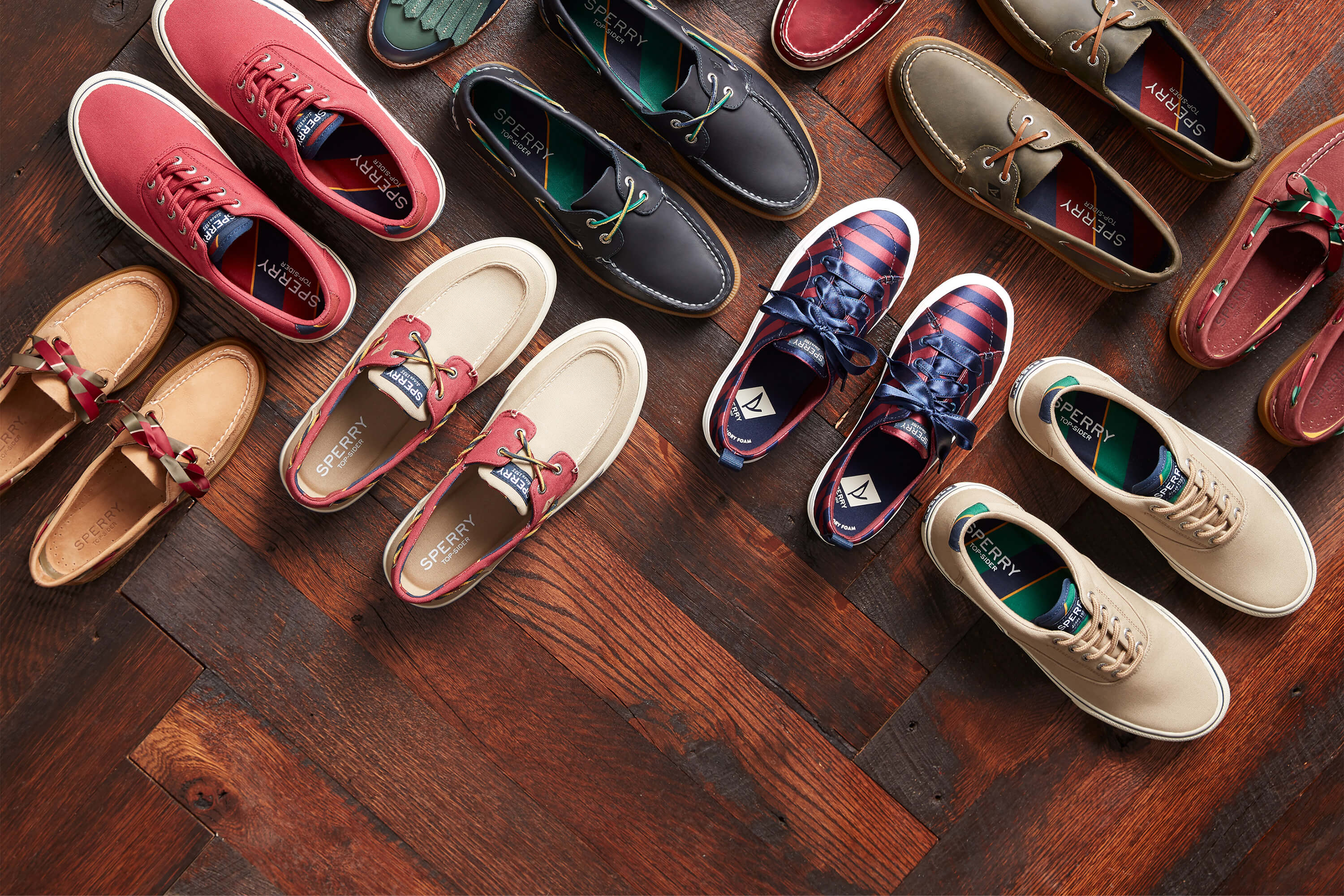 Many pairs of Varsity Classics laid out in a criss-cross fashion on a parquet floor.