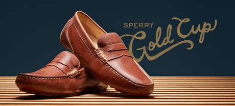 2 mens Sperry Gold Cup shoes lined up on a wood floor.