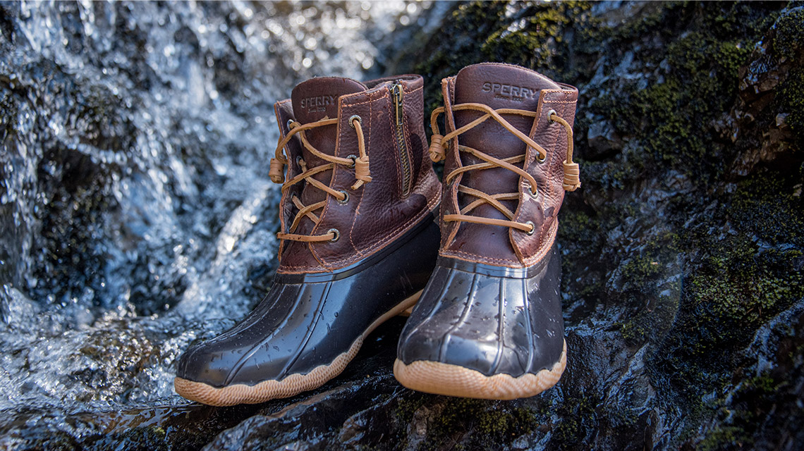 Blue Rubber and Brown Leather Duckboots on a rocky shoreline.