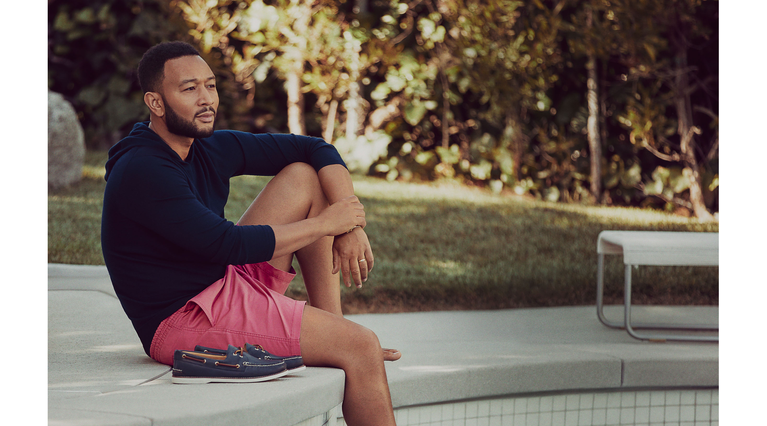 John Legend relaxing outside by his pool with the Gold Cup Authentic Original by his side.