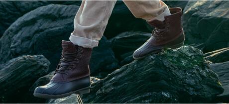 Feet in saltwater duck boots navigating across wet rocks, presumably by a shoreline.