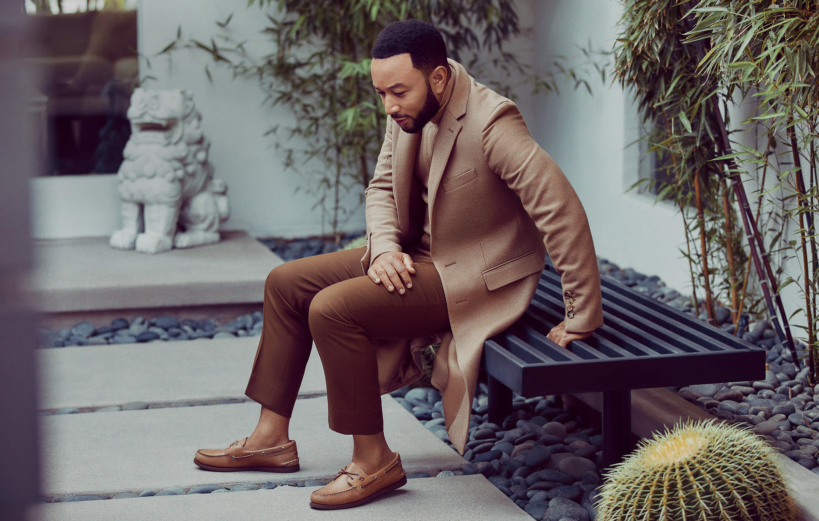 John Legend sits on a metal bench dressed in brown, wearing Sperry Authentic Original Leather Boat Shoes.