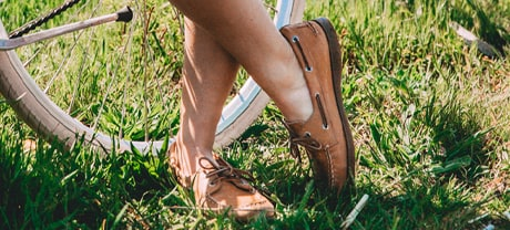 A womean wearing Sperry Authentic Original shoes, standing by her bike.