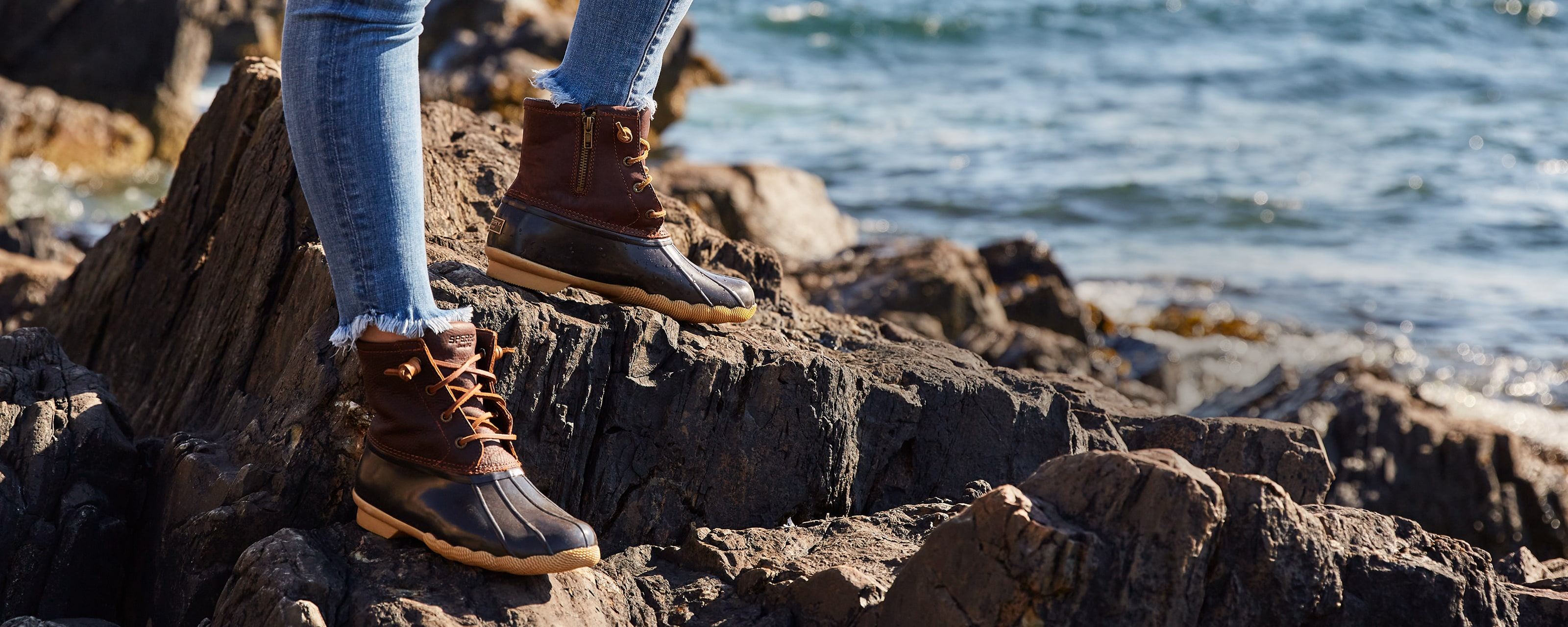 Person standing on the rocks by the ocean, wearing Sperry Saltwater boots.