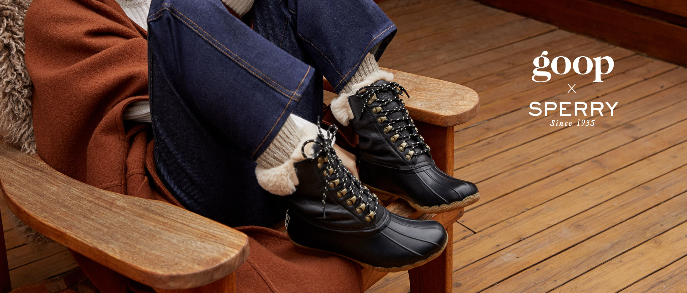 A person sitting in a wooden chair pulls up their feet wearing a pair of black goop x Sperry boots.