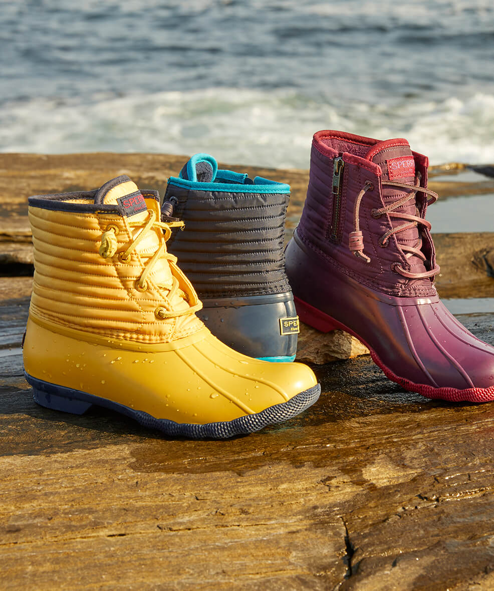 Bright-colored boots on rocks beside the ocean.