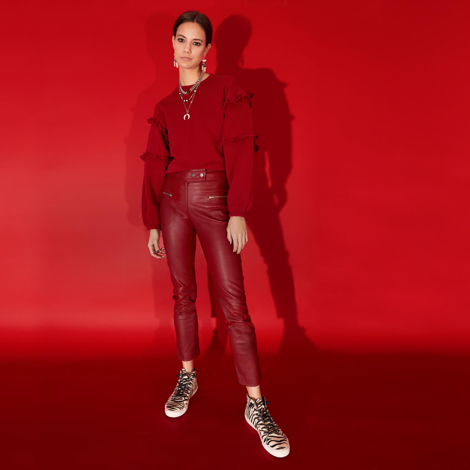 Model dressed in red against a red background wearing shoes from the Sperry x Rebecca Minkoff collab.