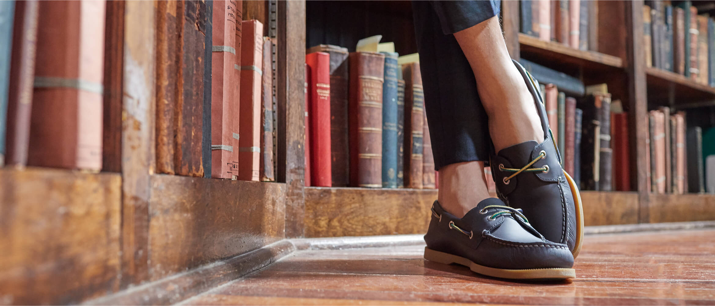 Someone leans against a bookshelf in a library. All we can see is their shoes. They're nice shoes.