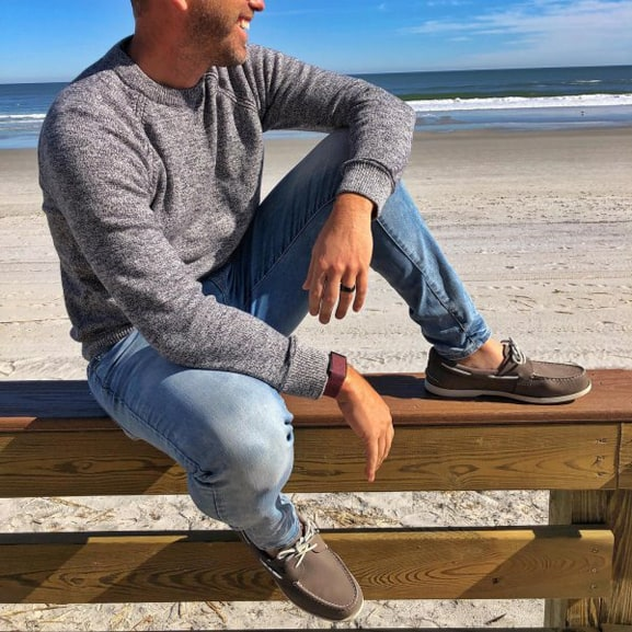 A man sitting on a wood bench by the ocean, wearing Sperry boat shoes.