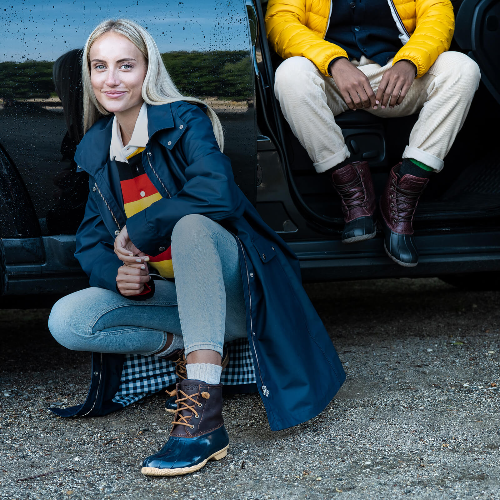 Crouching beside a car on gravel wearing blue Saltwater boots.