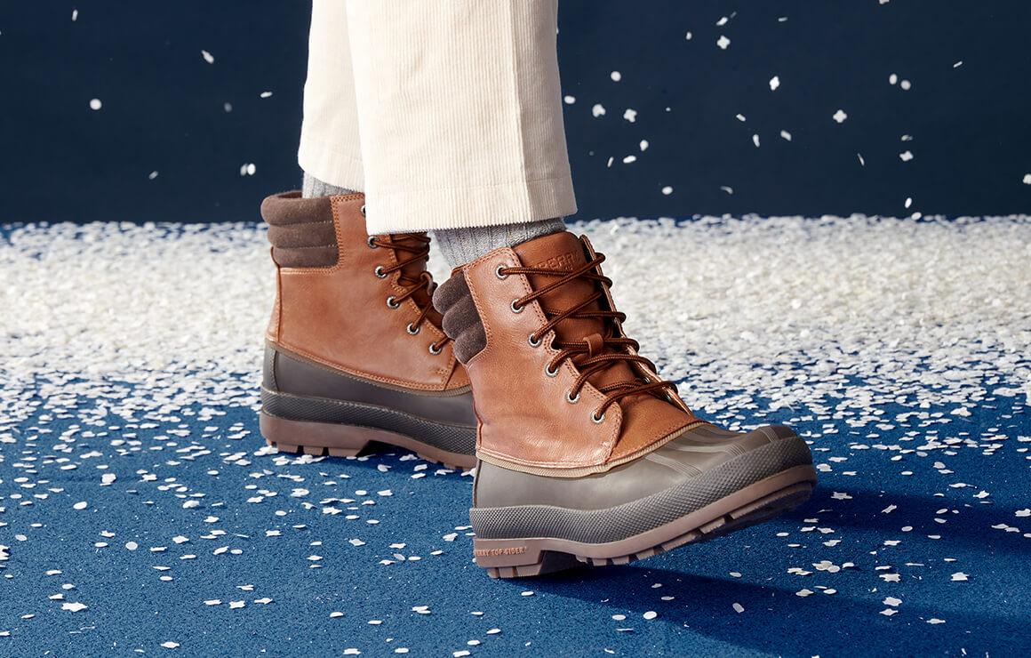 Wearing waterproof boots beside a Charlie Brown tree.