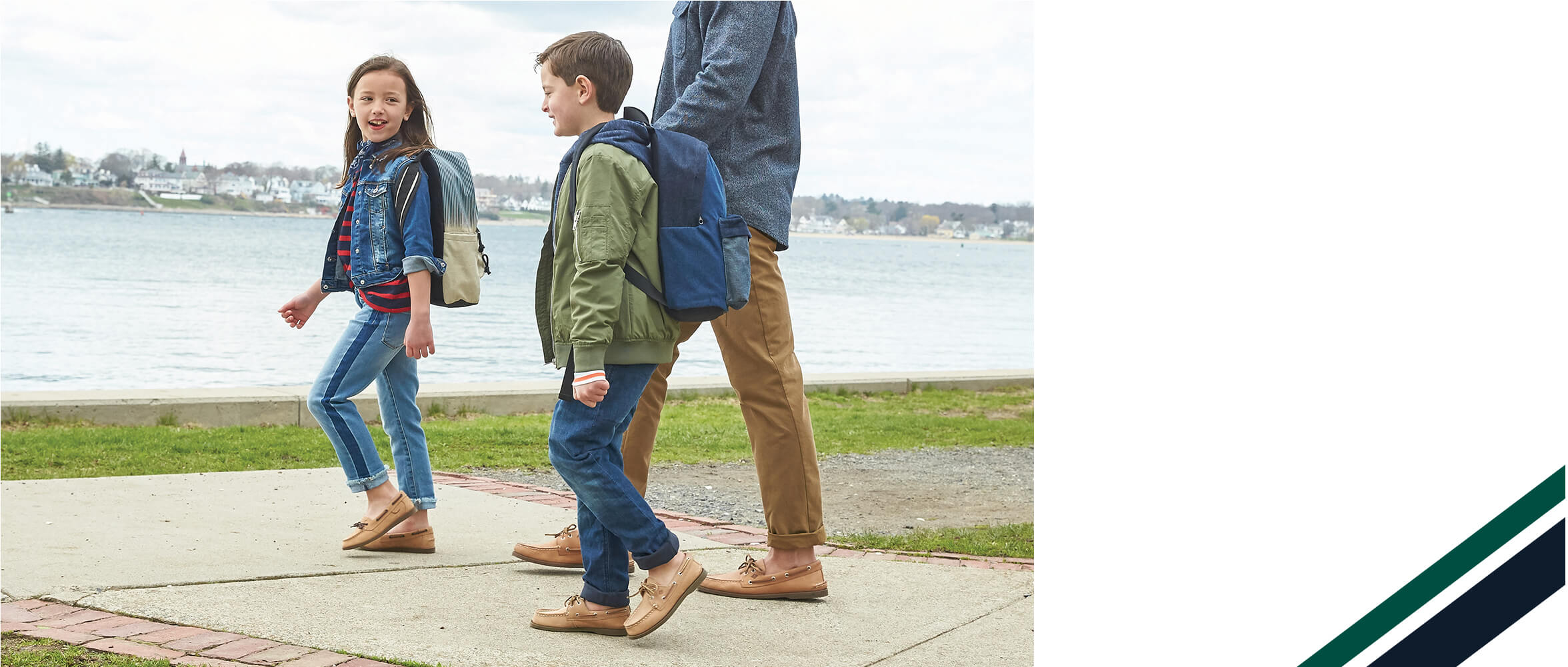 Kids walking along a dock, near water. They have nice shoes.