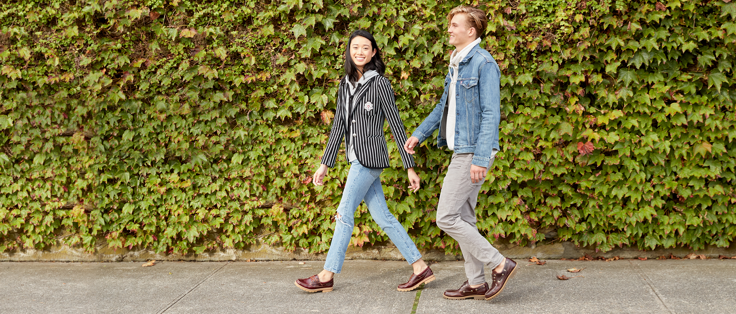 A man and woman walking in new lug boots with greenery in the background.