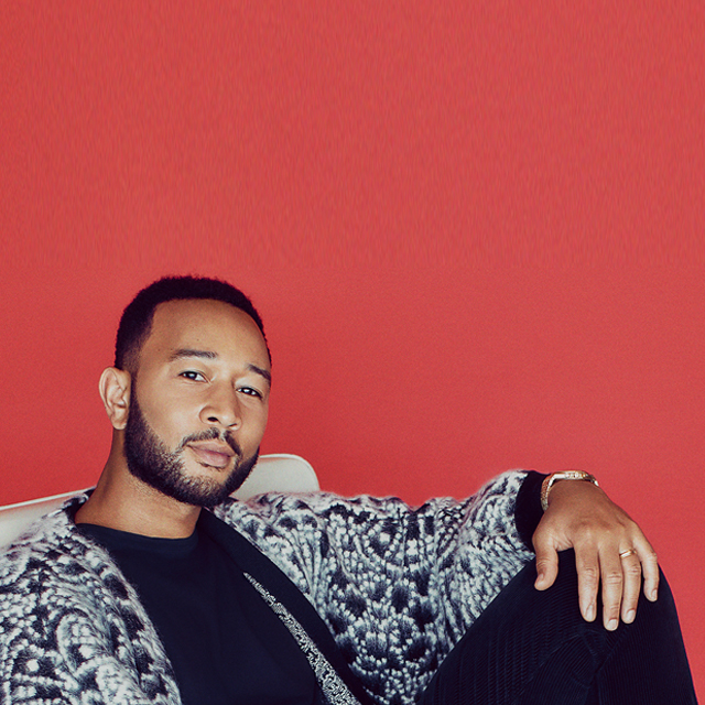 John Legend against a red background.