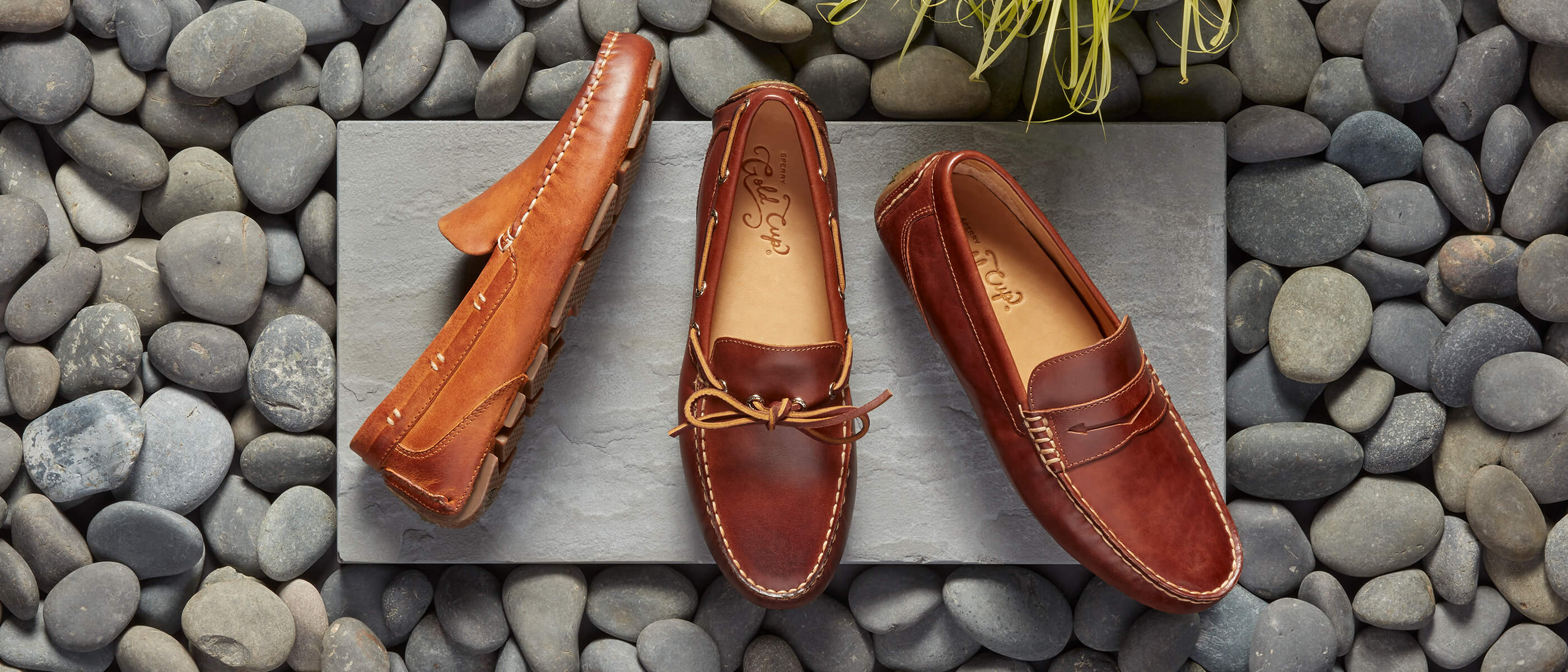 Three styles of Gold Cup loafers on a concrete slab surrounded by grey river stones and grass.