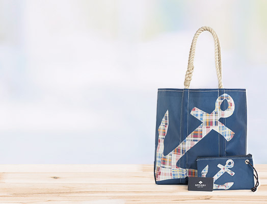 Blue tote asn wristlet purse on ground next to Sperry gift card.
