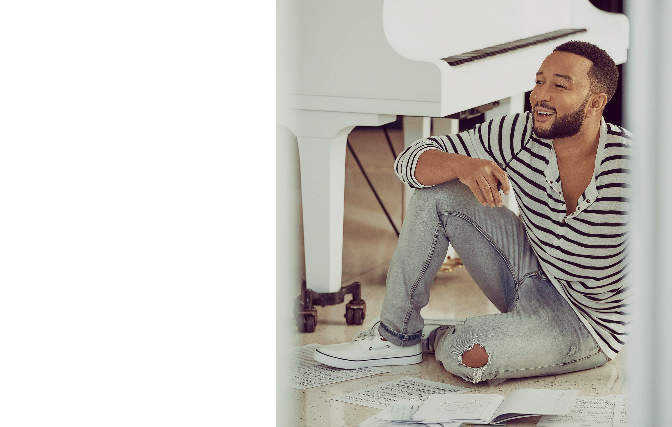John Legend sits on the floor beside a white piano surrounded by sheet music wearing Sperry Bahama II Sneakers.
