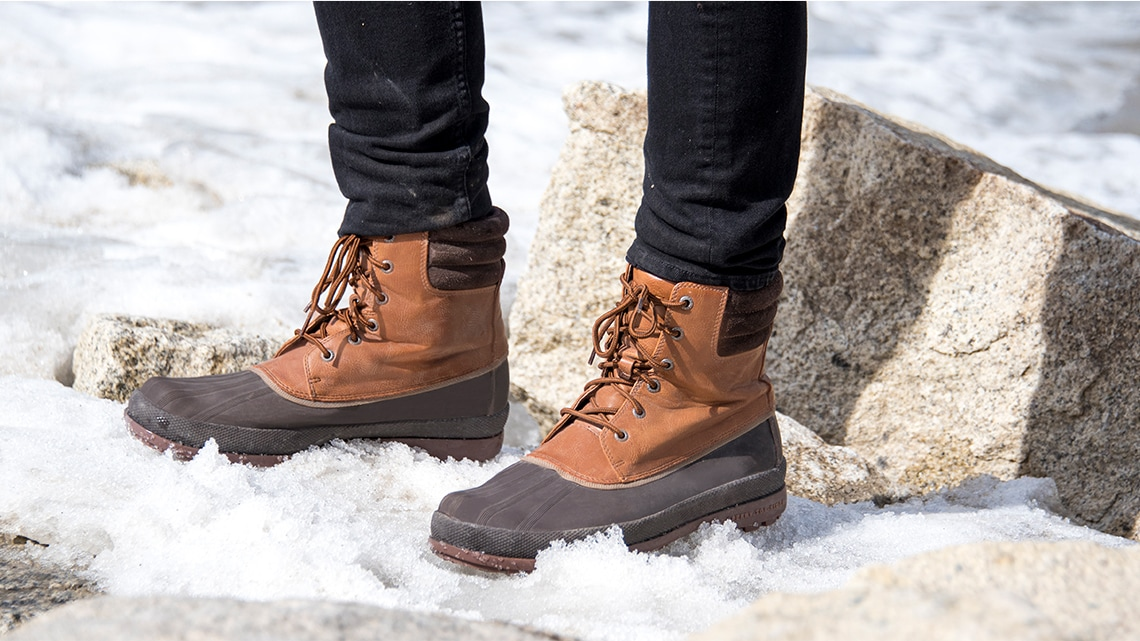 A man wearing Cold Bay duck boots standing in the snow