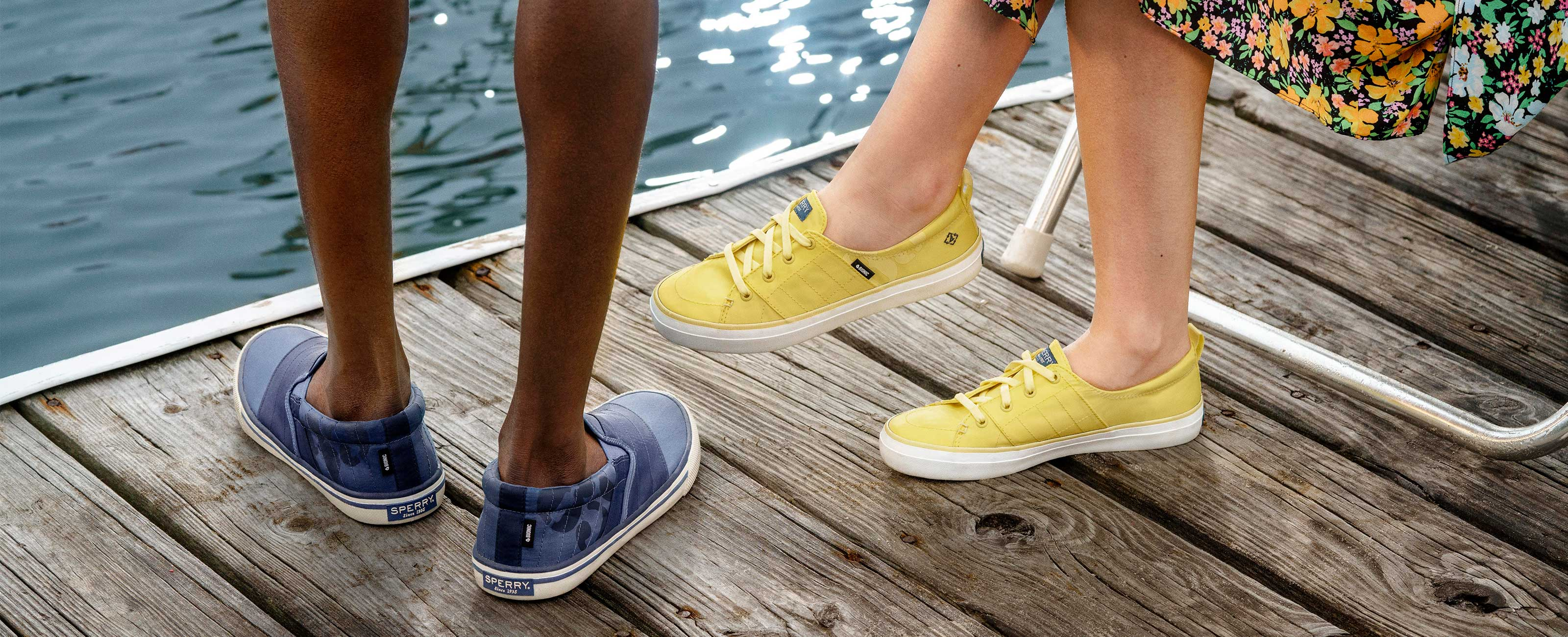 Close up of two pairs of feet wearing Sperry BIONIC shoes, while relaxing on a dock.