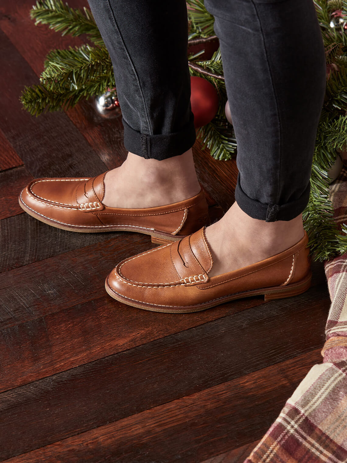 A pair of feet stand next to a christmas tree wearing Seaports without socks #chillyankles.
