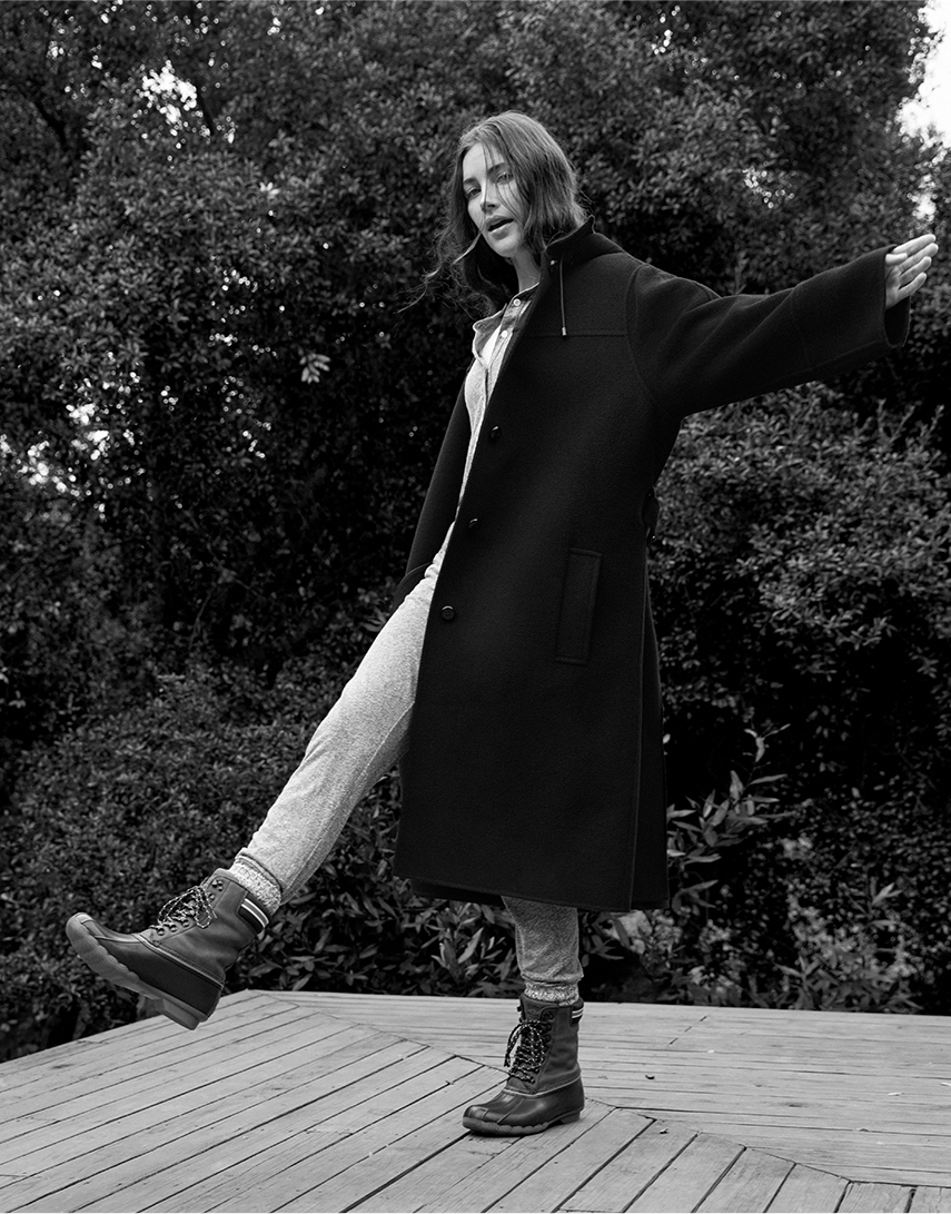 Woman wearing Goop & Sperry boots in a black and white photo.