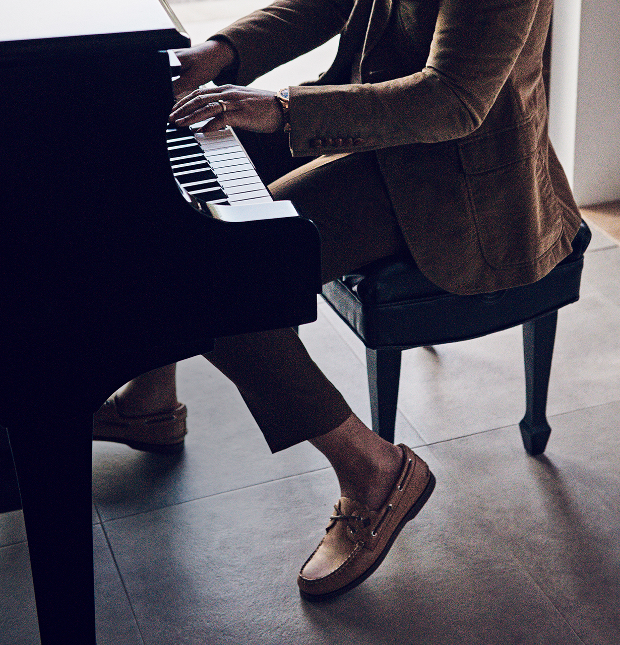 John Legend sitting on a piano bench, wearing Sperry Boat Shoes.