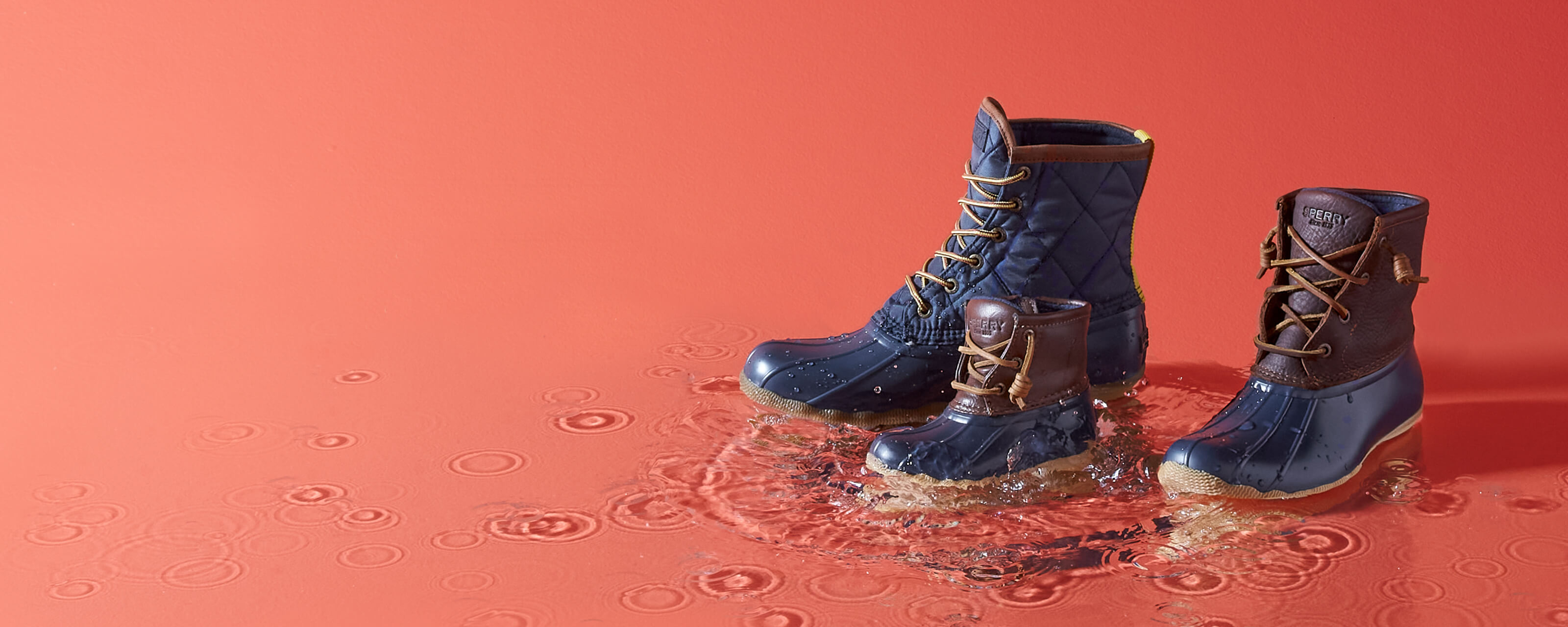 Three sizes of Saltwater boot standing in a puddle.