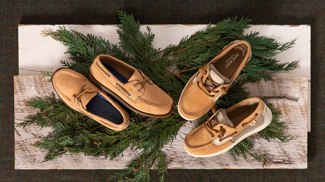 Sperry boat shoes in several colors stacked atop evergreen branches.