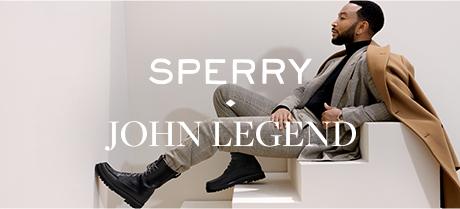 John Legend sitting on stairs.