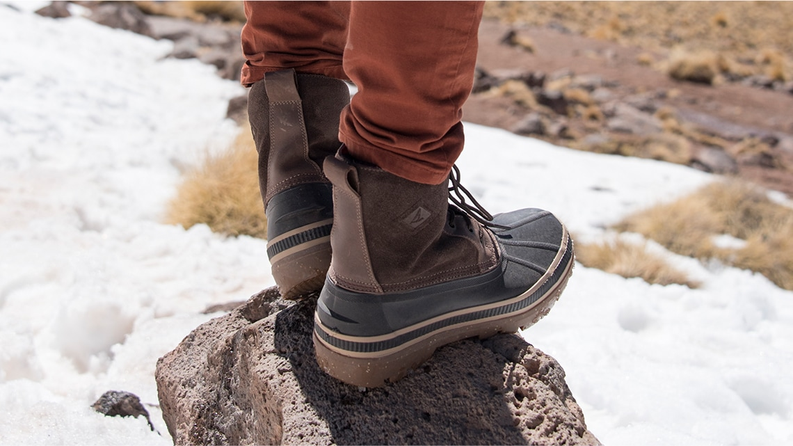 A man wearing Ice Bay duck boots standing on a rock in the snow