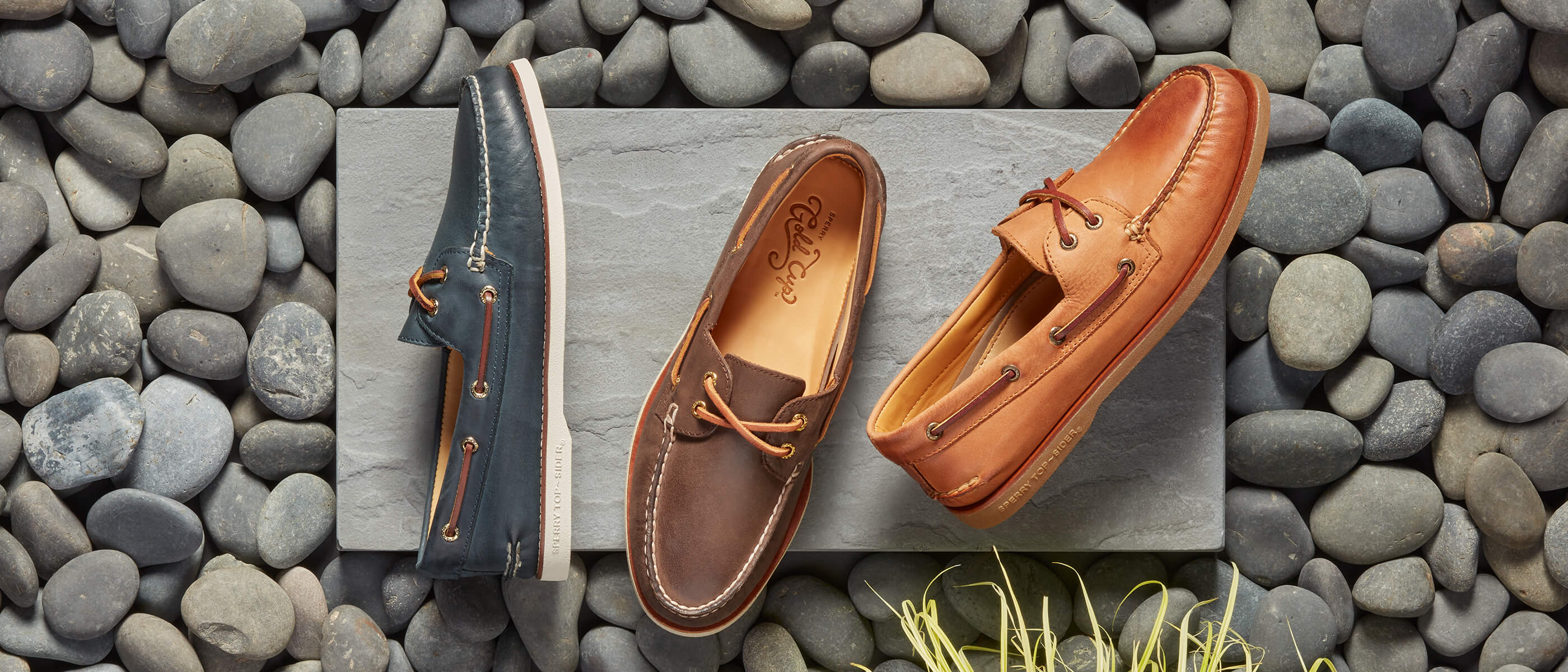 Three colors of Gold Cup boat shoes on a concrete slab surrounded by grey river stones and grass.