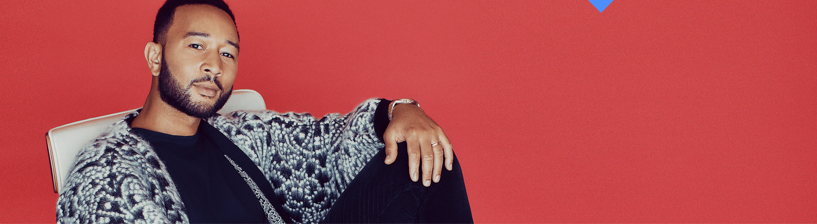 John Legend in a black and white sweater lounging on a red background