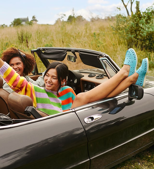 Two People in a convertible. The passegner has her feet up on the mirror, wearing blue Sperry Float shoes.