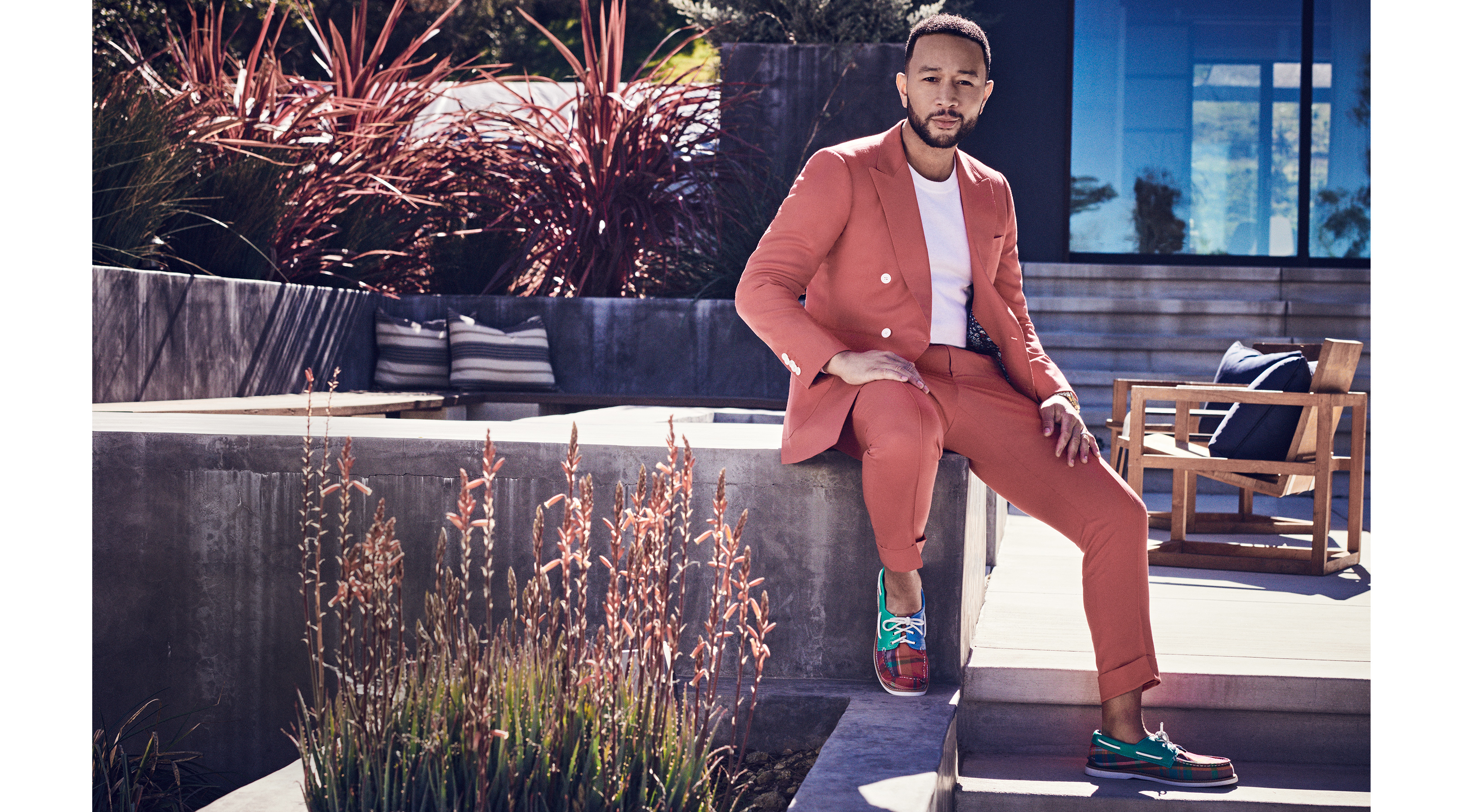 John Legend relaxing outside on his patio, wearing Sperry Cloud Authentic Original Plain Boat Shoes.