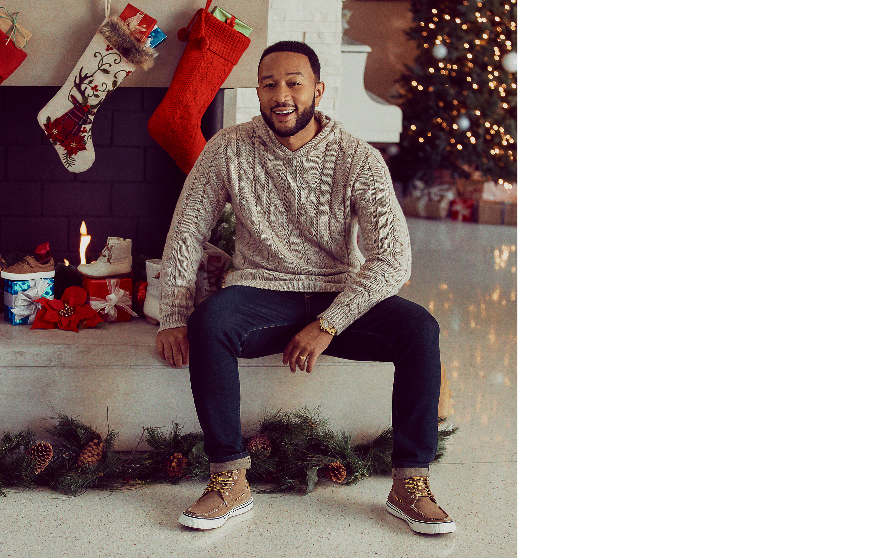 John Legend sitting on his fireplace wearing Sperry Bahama Storm Boots.