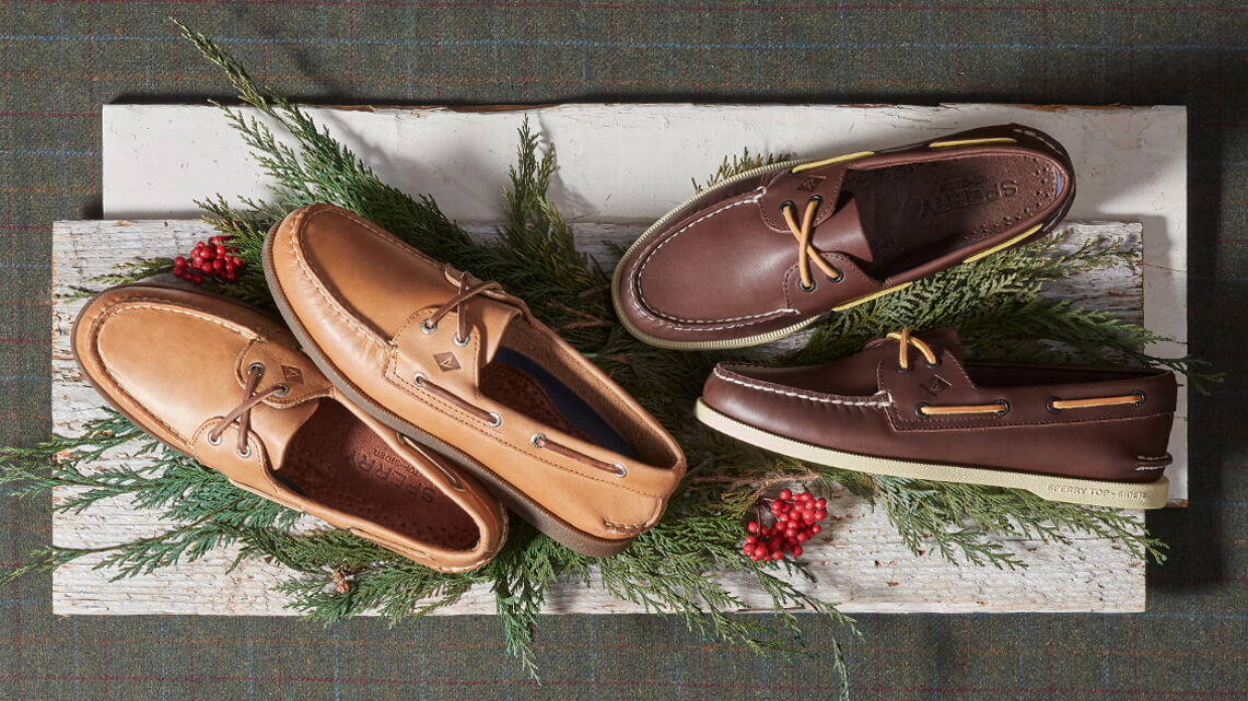 Sperry Authentic Originals in several colors stacked atop evergreen branches with red berries.