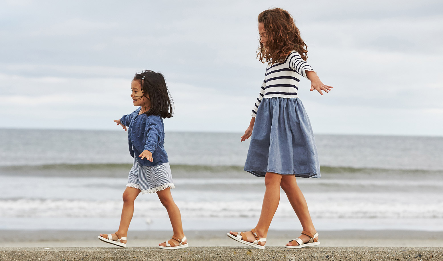 a2562d8c724579 Two kids walking along the shoreline in their sandals.