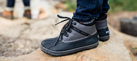Close up of duck boots on little feet, standing on a rock.